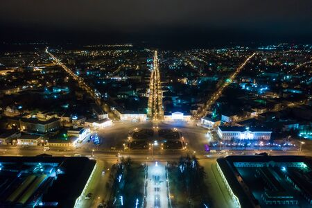 Night view of city center Kostroma with car traffic and illuminated Fire tower, Russia.