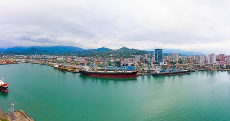 panorama of the port of Batumi and ships at the mooring wall. Bulk cargo ship under port crane, Batumi seaport, Georgia.