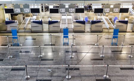Empty international airport building, lack of passengers during the global crisis and diseases. Empty row check-in desks in international airport.