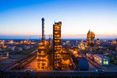 Oil refinery plant industry, Refinery factory. oil storage tank, rectification column and pipeline against the backdrop of sunset in summer, Russia.