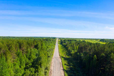 bad asphalt road with large holes top view, federal highway of the Vologda and Kostroma regions in the north of Russia.