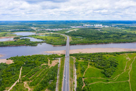 Panorama of the Kirov city and Oktyabrsky district in the nord part of the city of Kirov on a summer day from above. highway across the bridge over the Vyatka river at the entrance to the city.