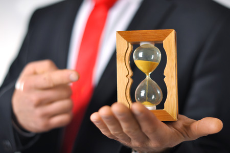 Man in a suit with tie holding an hourglass Imagens