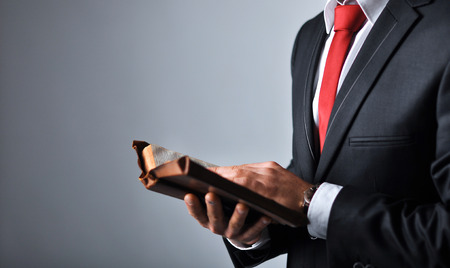 law suit: Businessman in a suit holding a book