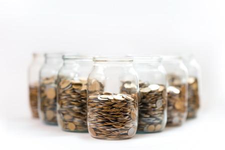 banco dinero: monedas en un per�odo de tres frascos de vidrio sobre un fondo blanco
