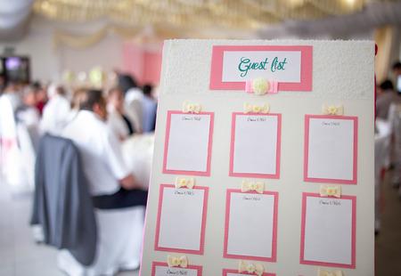 Bordo bianco originale con decorazioni e nastri rosa e una lista degli invitati