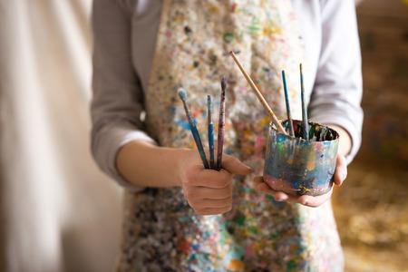 Primo piano di artista femminile mano che tiene il pennello