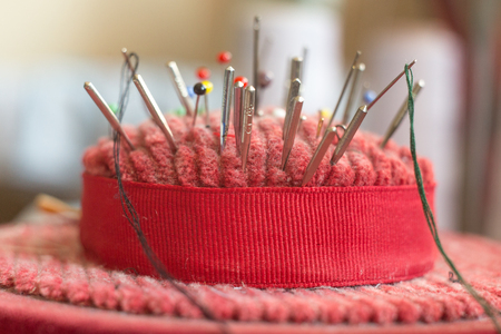 needle: pincushion with lot of needles and pins for sewing