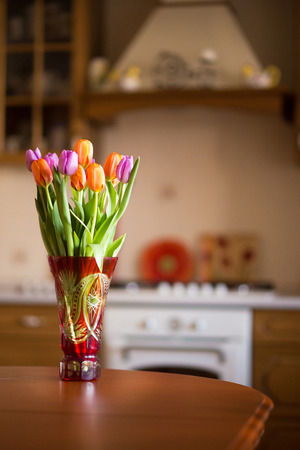 fresh pink and purple tulips on kitchen background Imagens