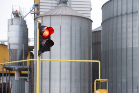 traffic lights and agricultural grain elevator building for grain storage and railroad