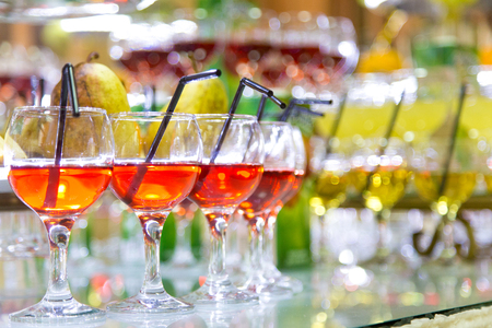Glasses of cocktails on party background