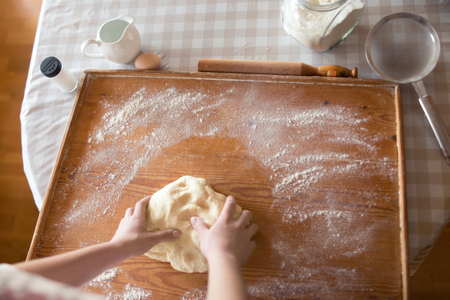 Baker hands kneading dough in flour on table Imagens