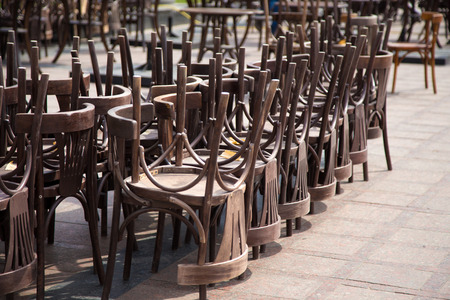 old wooden chairs and vintage chairs, one on the street