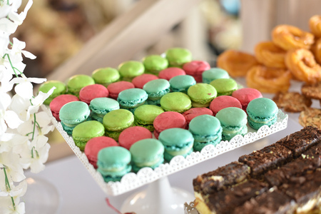 Wedding decoration with colorful cupcakes, cake and macarons. Wedding dessert table