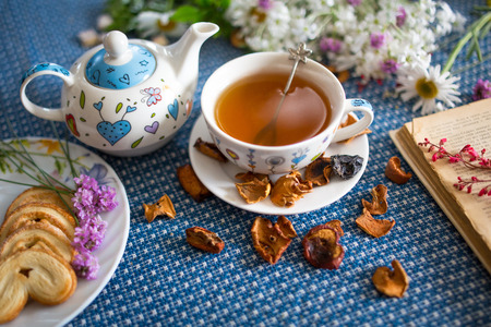 cup of tea with book and flower Imagens