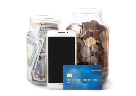 jar with coins and money, credit card and phone