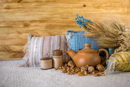 Clay teapot with wheat ear, pillow and nuts on the cloth background