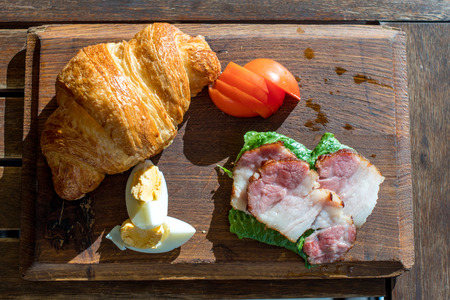 Breakfast with eggs, bacon, croissant and tomato on wooden tray, overhead view