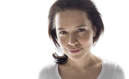 Studio headshot of young attractive woman smiling gently