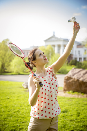 attractive young woman playing badminton in a park