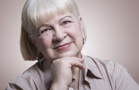 Headshot portrait of an amiable elderly woman smiling in a studio Stock Photo