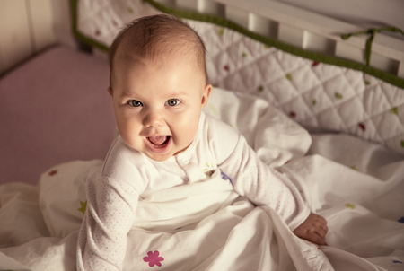 Cute baby sitting in a bed