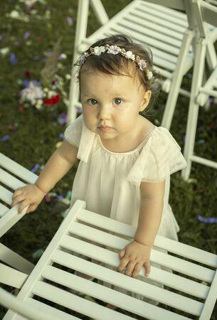 Cute baby girl in white dress on a family wedding Foto de archivo - 129951870
