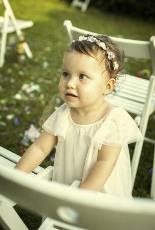 Cute baby girl in white dress on a family wedding Foto de archivo - 129951871
