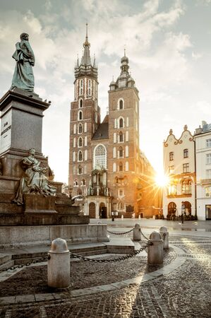 Adam Mickiewicz monument and St. Mary's Basilica on Main Square in Krakow, Poland Фото со стока