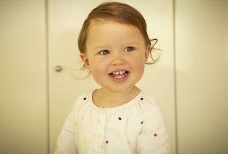 Cute little girl with blond hair laughing Фото со стока
