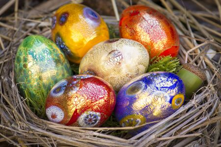 Six colorful painted Easter eggs in a nest