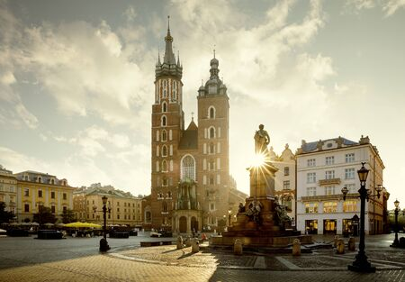 Cityscape of Krakow town square with Adam Mickiewicz monument and St. Mary's Basilica, Poland Фото со стока