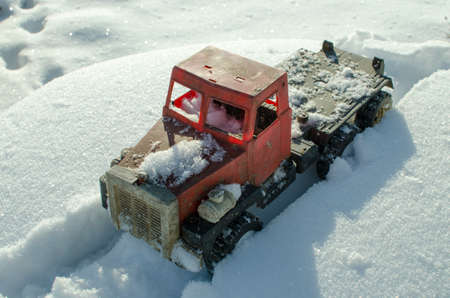 A toy truck trapped in the snow, closeup shot, concept of driving in winter