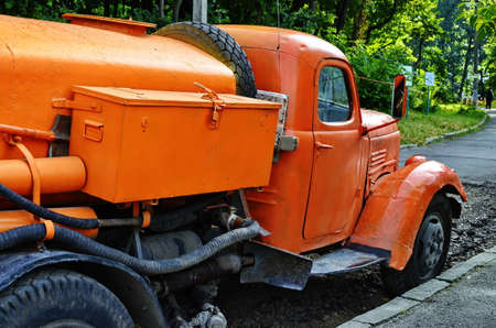An old retro water truck based on a truck. Fragments of an orange car.