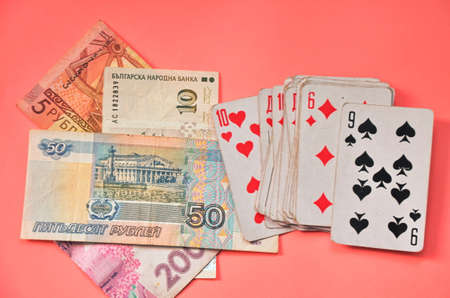Playing cards and money from different countries on a pink background.