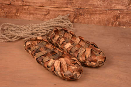 Bast shoes on wooden fence.Museum ekskonat-copy of an ancient wicker shoes.