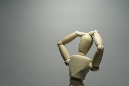 A mannequin with hands over head