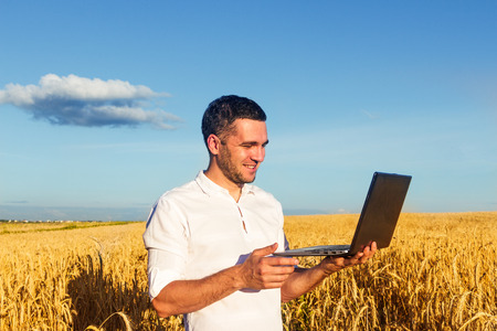 Young handsome young man solves issues related to his big business in the middle of the field using a laptop. The concept of a happy landowner of a farmer who calculates the profit from a good harvest Stok Fotoğraf