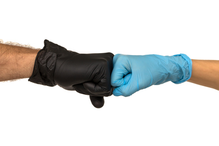 man and a woman in multi-colored rubber gloves shake hands with each other. Isolate on a faded background. The concept of a successful team of doctors interns interns