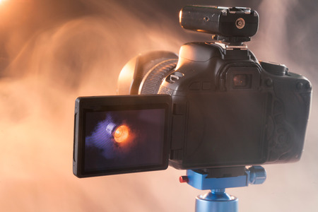 Photo of the camera on a blue tripod that photographs in the studio a professional lighting device in the smoke. Studio lights and smoke equipment. Camera with radio synchronizer