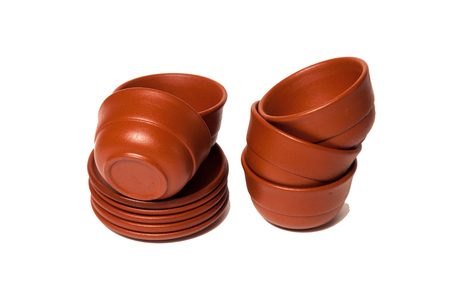 Stack of brown clay cups and plates. The concept of tea ceremony, breakfast, tea