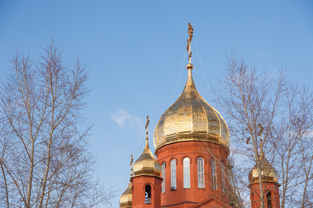 Old red brick Christian church  in Kemerovo with golden and gilded domes against a blue sky and tree branches. Concept of faith in god, orthodoxy, prayer