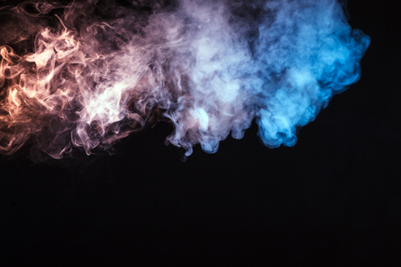 Colored smoke on a black background. The concept of a light show at a music concert Stock Photo