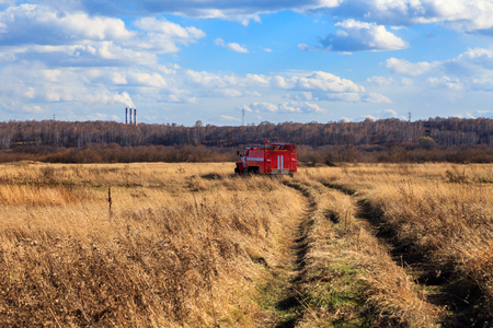 Red firetruck car Ural rides through the autumn field with yellow and faded grass against the blue sky and clouds. The concept of extinguishing forest fires in California