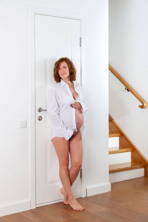 Caucasian Future mum - standing near door. Beautiful portrait pregnant brunette in lingerie at home. Girl dressed in a white shirt, lace underwear