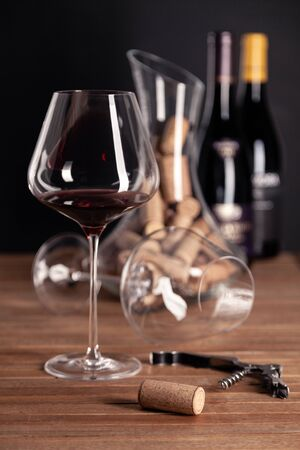 Crystal shiny glass of red wine, bottles, corkscrew, opener, sommelier knife, transparent decanter, corks on wooden table. Closeup, vertical, selective focus side view. Concept wine magazine photo