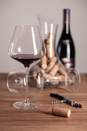 Crystal red wine glass, bottle, corkscrew, opener, sommelier knife, transparent decanter, corks on wooden table. Closeup, vertical, selective focus, side view. Concept degustation in winery cellar