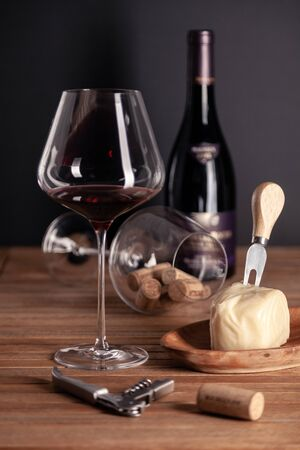 Pouring red wine in crystal glass, bottle, corkscrew, opener, sommelier knife, transparent decanter, corks, cheese on wooden table. Closeup, vertical, side view. Concept degustation winery cellar