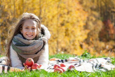 Portrait of beautiful little girl on autumn picnic. Little girl hold fruit in on background gold forest. Toddler eating fruits at harvest. Outdoor fun for children. Healthy nutrition. Family