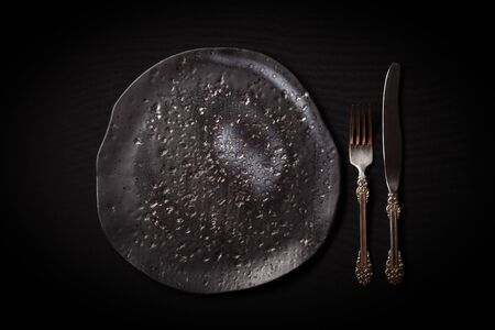 Closeup empty round black aged ceramic plate, vintage cutlery - fork, knife on dark background with copy space. Concept modern shooting menu, restaurant advert, tableware catalog, top view, copy space